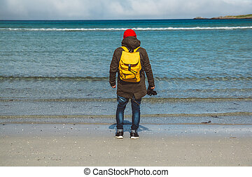 Traveler is a professional photographer taking over the landscape photo landscape. Wearing a yellow backpack in a red hat standing on a sandy beach on the background of the sea. Shoot from the back.