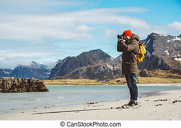 Traveler is a professional photographer taking over the landscape photo landscape. Wearing a yellow backpack in a red hat standing on a sandy beach on the background of the sea and mountains. Lifestyle Travel Concept.