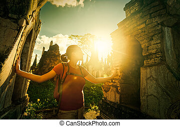 Traveler looks at sunset ancient Buddhist stupa of the temple complex In Dein, Inle Lake. Birma