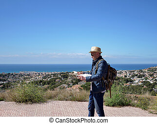 Traveler man on top of a mountain with a map in his hands, against the backdrop of a city by the sea