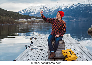 Traveler man taking self-portrait a photo with a smartphone. Tourist in a yellow backpack sitting on wooden pier a background of a mountain and a lake. Traveler walks, takes photo in the mountains.