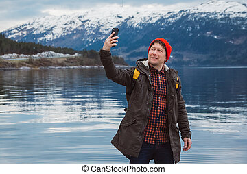 Traveler man taking self-portrait a photo with a smartphone. Tourist in a yellow backpack standing on a background of a mountain and a lake. Traveler walks, takes photo in the mountains.