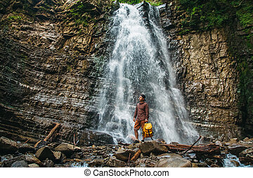 Traveler man with a yellow backpack standing on the background of a waterfall. Travel lifestyle concept.