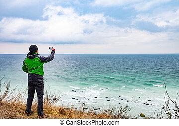Traveler man with phone takes photo of  coast - Traveler man...