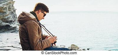 Traveler man with photo camera sitting on coast