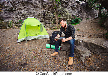 Traveler near a tent with a tablet in the evening. Rocky mountains background