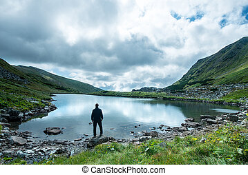 Traveler on the shore of a mountain lake