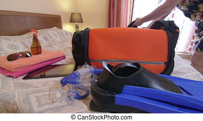 Traveler packing clothes in travel bag for summer beach vacation