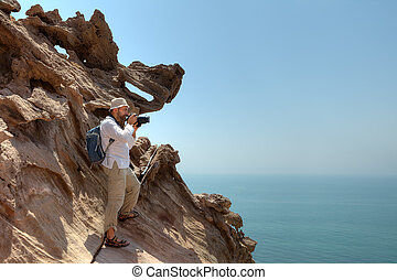 Traveler photographing nature, standing on edge of the cliff.