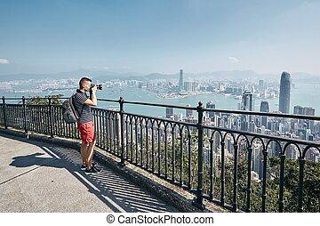 Traveler photographing urban skyline - Young man (traveler)...