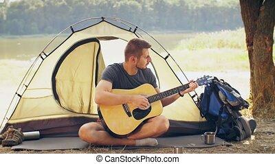 Traveler play guitar on nature