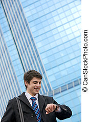 Portrait of smart businessman looking at his watch with happy expression