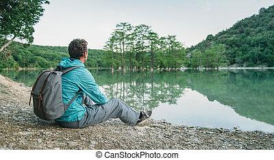 Traveler restring on coast of lake