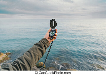 Traveler searching direction with a compass on coast near ...