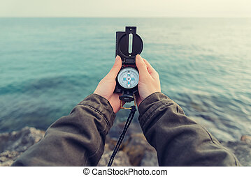 Traveler searching direction with a compass on coast