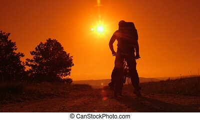 mountain bike against sun - Traveler silhouette on mountain...