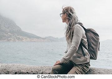 Traveler sitting on coast