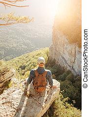 Traveler sitting on edge of cliff.