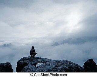 Young male traveler sitting on the sandstone cliff. Rear view of male hiker in hat and green jacket siton the rocky peak while enjoying a daybreak above mountains