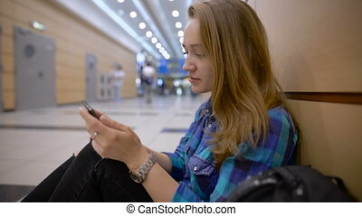 Traveler standing woman using a smart phone and waiting in an airport