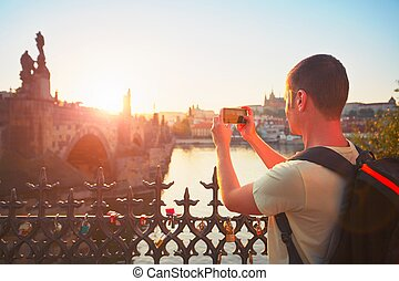 Traveler with backpack taking photo by mobile phone. Young tourist near Charles bridge at the sunset. Prague, Czech Republic. - back lit