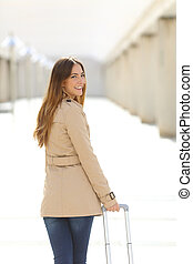 Traveler tourist woman walking and looking at camera in an airport