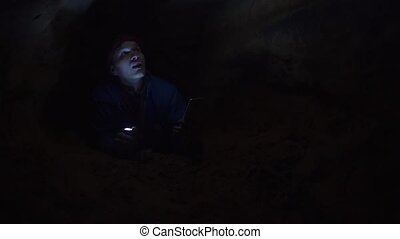 Traveler using smartphone laying on ground in tight hole in cave with flashlight
