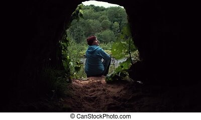 Traveler using smartphone sitting near exit from cave. Forest at background.