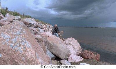 Traveler walking on rocky beach slope