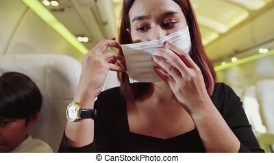 Traveler wearing face mask while traveling on commercial airplane . Concept of coronavirus disease or COVID 19 pandemic outbreak effects on tourism and airline business .