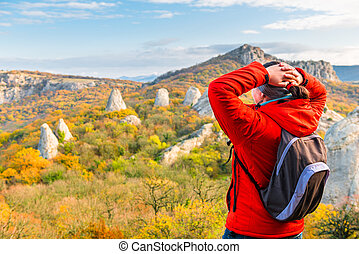 traveler with a backpack in the mountains admires the autumn forest