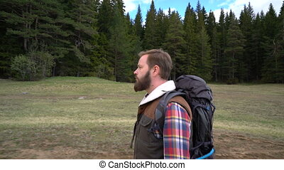 Traveler with a backpack walking along the lake - Bearded...