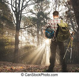 Traveler with backpack, hiking poles and sleeping bag  in autumnal forest