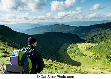Traveler with backpack on the mountains