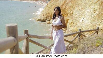 Traveler with phone enjoying ocean - Beautiful young woman...