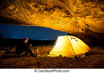Traveler with smartphone near the glowing camping tent in the night grotto under a starry sky