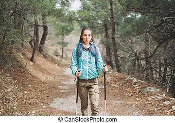 Traveler with trekking poles outdoor