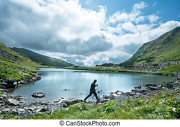 Traveler with trekking poles walks on the shore of a mountain lake