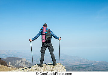 Traveler with trekking sticks and a backpack on the top of the mountain
