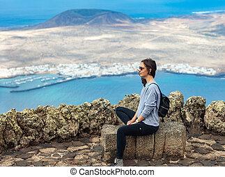 Traveler woman enjoying at viewpoint on island. Travel vacation concept. La Graciosa Island, Mirador del Rio, Lanzarote, Canary Islands, Spain.