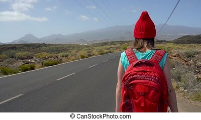 Traveler woman hitchhiking on a sunny road and walking....