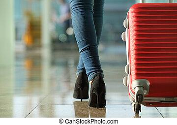 Traveler woman legs walking carrying a suitcase