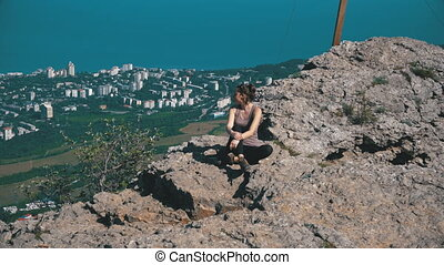 Traveler Woman Sits on Top of a Rocky Mountain