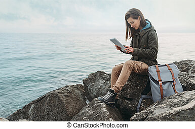Traveler woman sitting on coast with digital tablet
