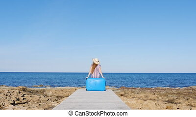 Traveler woman sitting on her suitcase on the beach