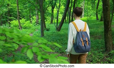 Traveler woman with backpack walking in the forest.
