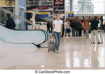 young woman walking with suitcase in an airport