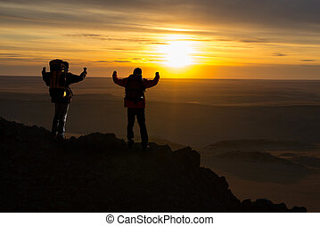 Two hikers climb in the mountains of the sunset