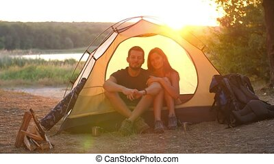 Travelers in a tent - Young couple resting in camping tent...