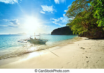 Travelers meet the sunset on a wild beach against the islands of El Nido. Philippines.